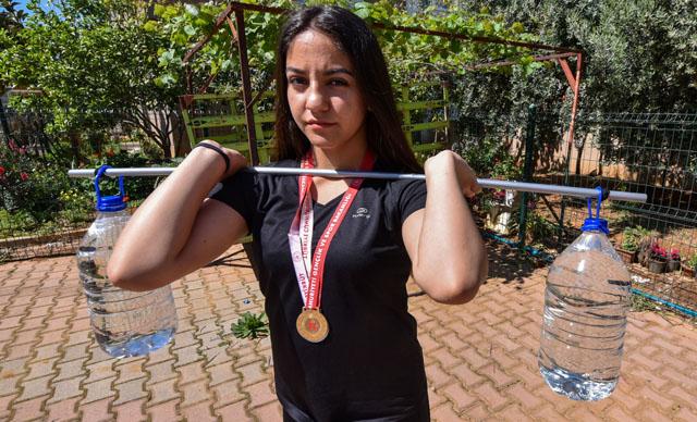 Şampiyon halterci, 5 litrelik su bidonlarıyla güç depoluyor